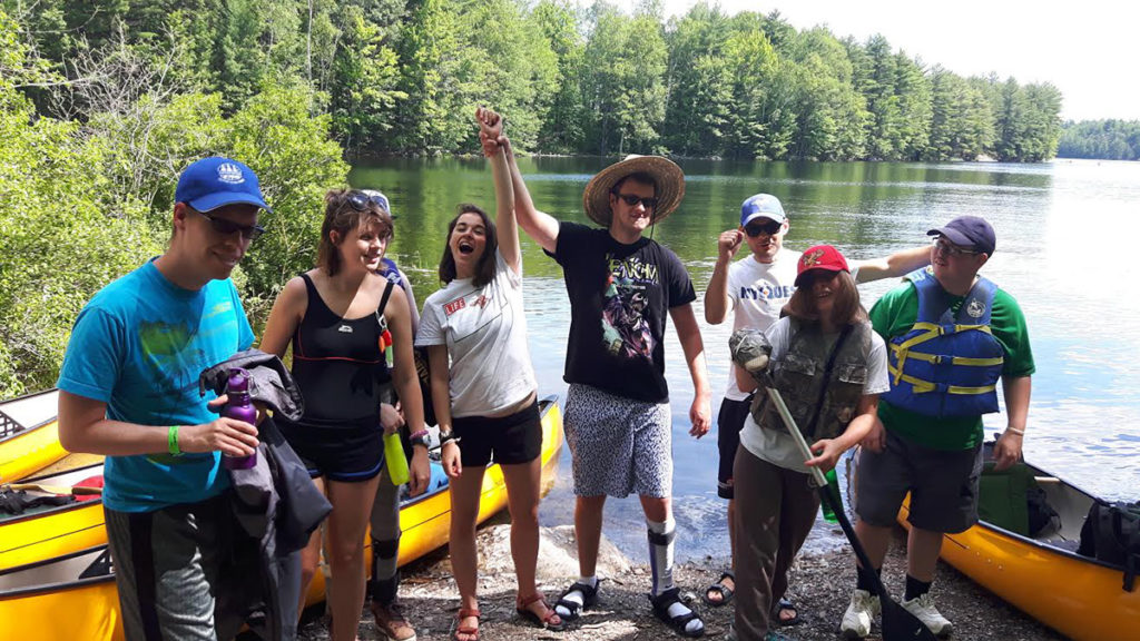 Out-tripping Adventure Camp - Campers pose on the shoreline by their canoes