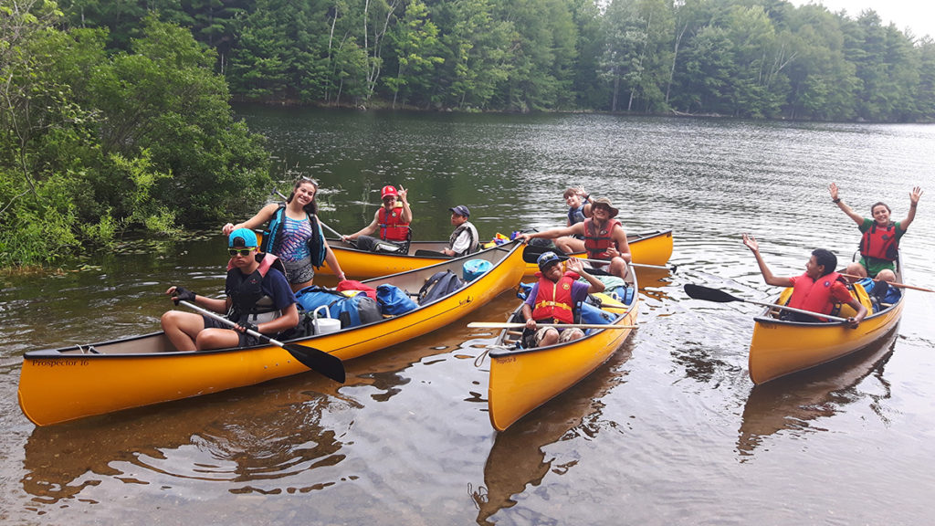Out-tripping Adventure Camp - A brigade of canoes paddle twards shore