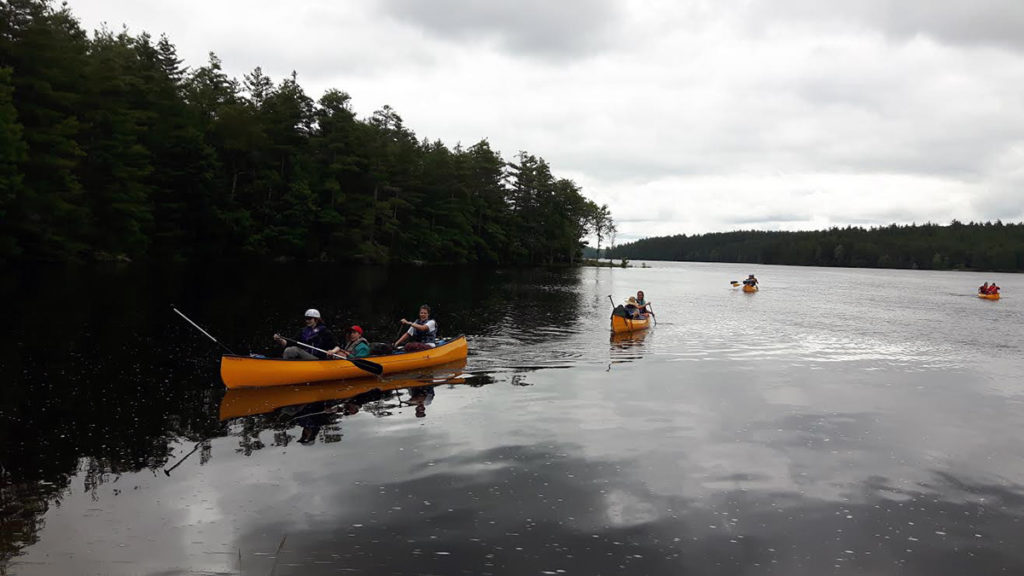 Out-tripping Adventure Camp - Orange canoes paddle in a row on gray water under a gray sky.