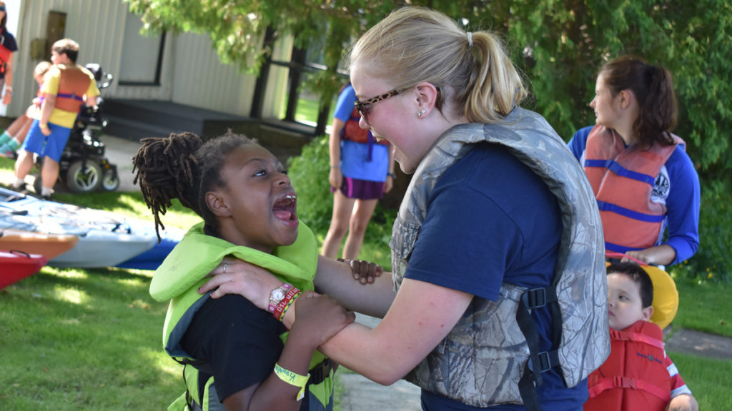 Discovery Camp - A councilor helps a camper with her life jacket