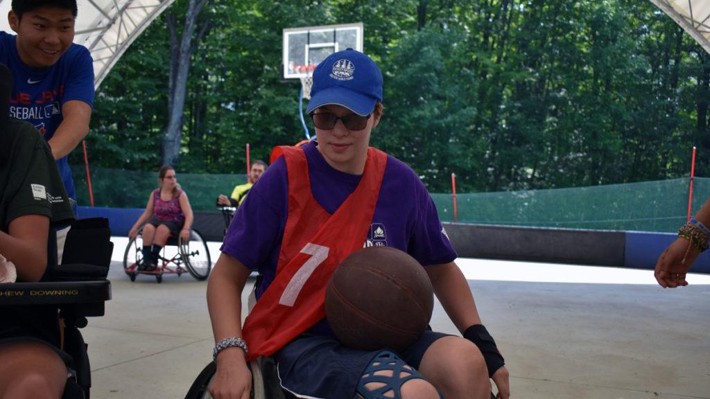 Sports Camp - A boy in a wheelchair enjoys basketball