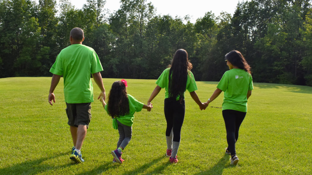 Family Camp - A family walks away in a green field wearing matching t-shirts