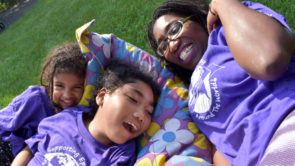 Family Camp - A mother and daughters smile while lying on the grass